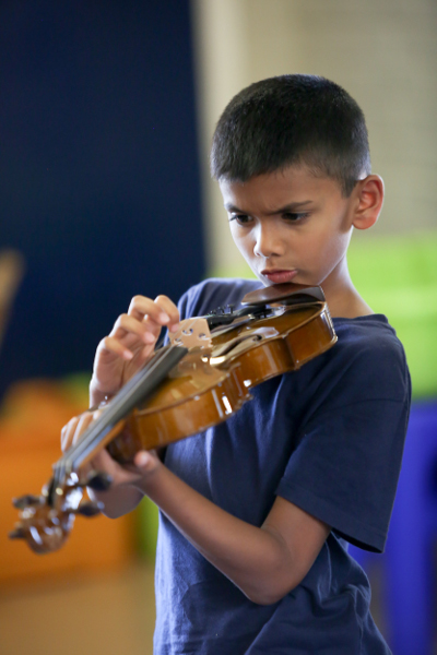 young boy learning violin