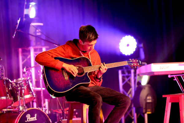 student playing guitar on stage