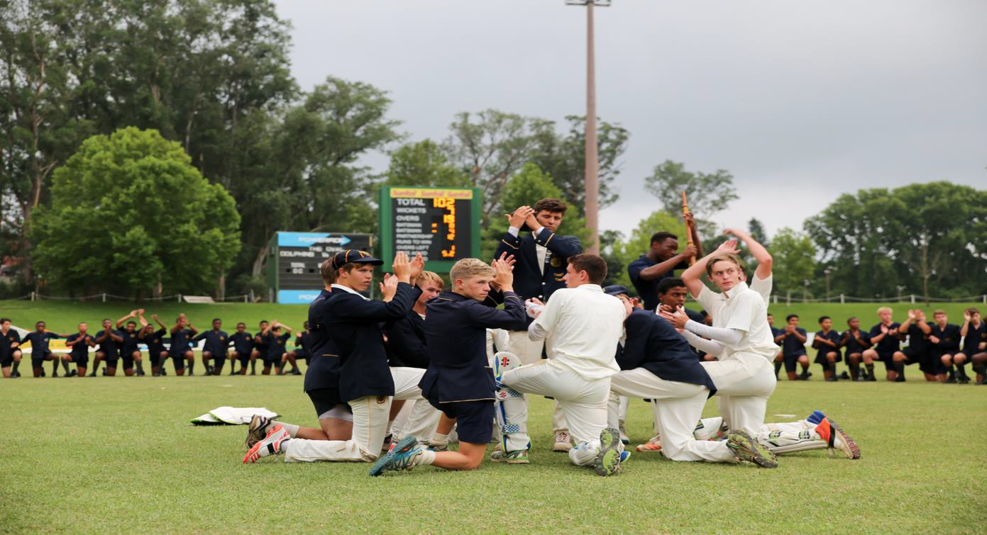 cricket team in a huddle on the field
