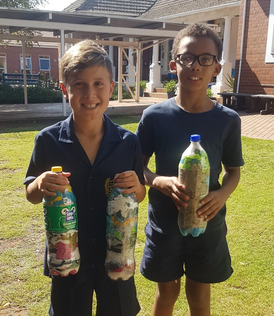 students holding eco bricks