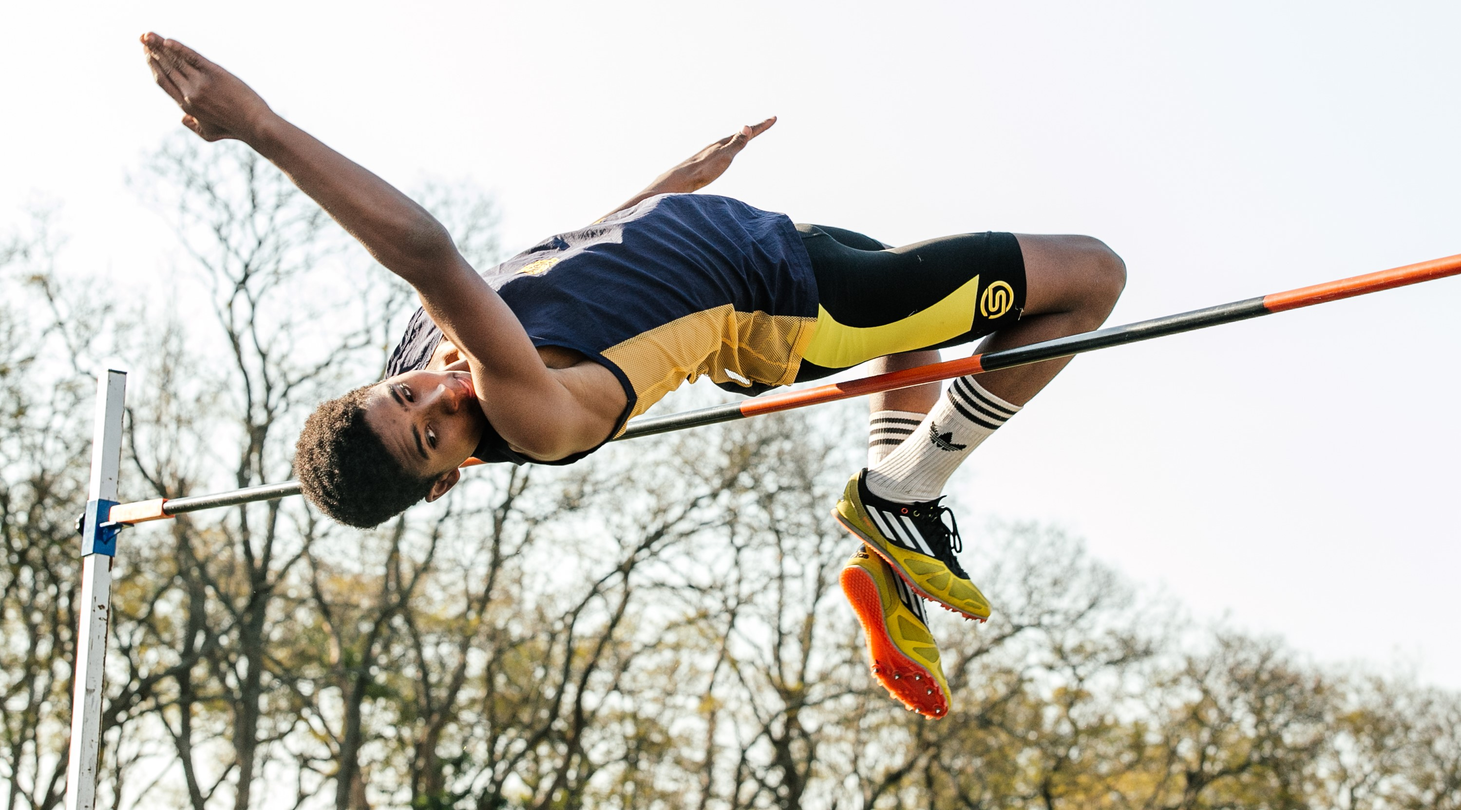 high school boy clearing the high jump in athletics